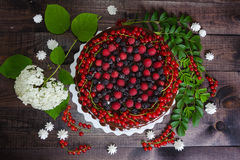 Cake with red currants, raspberries and blackberries. Cake with red curraunts, raspberries and blackberries on a wooden background Royalty Free Stock Image