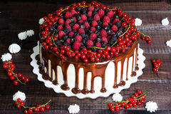 Cake with red currants, raspberries and blackberries. On a wooden background Royalty Free Stock Photography