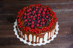 Cake with red currants, raspberries and blackberries. On a wooden background Royalty Free Stock Photos