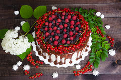 Cake with red currants, raspberries and blackberries. On a wooden background Royalty Free Stock Images