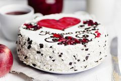 Cake with a red heart and pattern. Delicious cake with a red heart and pattern on a light background stock photo