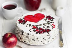 Cake with a red heart and pattern. Delicious cake with a red heart and pattern on a light background stock photos