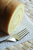 Cake roll and fork. A cake roll and a metal fork rest on clean paper and grass mat Stock Photos