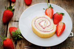 Cake roll with strawberries and cream cheese. On a dark wood background. tinting. selective focus stock photos