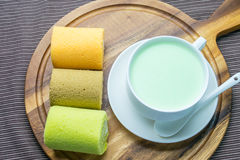 Cake rolls on wooden plate. With green tea Stock Image