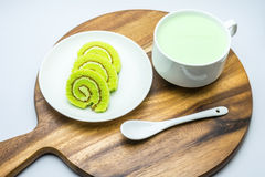Cake rolls on wooden plate. With green tea milk Stock Images