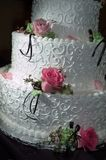 Cake with Roses. A wedding cake with roses resting on each teir.  Dramatic lighting helps show the detail in the icing while still showing detail in the roses Stock Photo