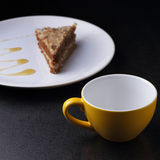 Cake on round white plate and yellow cup Royalty Free Stock Images