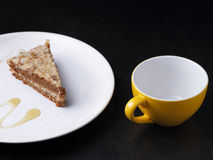 Cake on round white plate and a yellow cup Royalty Free Stock Photos