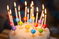 A cake and it's candles that read happy birthday Royalty Free Stock Image