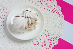 Cake on a saucer. Meringue with cream on the patterned napkin stock photos