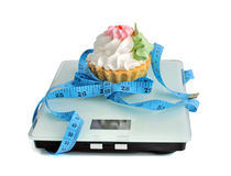 Cake on the scales measuring tape wrapped Royalty Free Stock Images