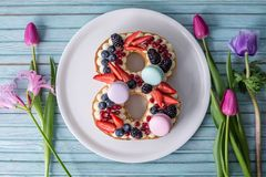 Cake in shape of number 8 decorated with berries and flowers tulips. Dessert for women's day on the eighth of March royalty free stock images