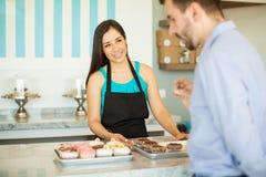 Cake shop employee showing cupcakes Royalty Free Stock Image