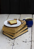 Cake slice on books. On a wooden background Royalty Free Stock Images