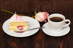 Cake slice and coffee cup with rose on wooden background Stock Images