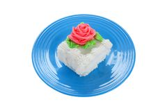 Cake Slice. With flower decoration on blue plate. Isolated on white royalty free stock images