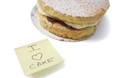 Cake slice with 'I love cake' sign on sticky notepaper Stock Images