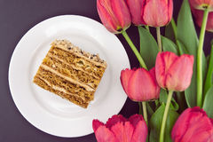 Cake slice with nut on plate. Bouquet of tulips. Top view.  Stock Photo