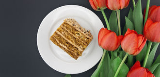 Cake slice with nut on plate. Bouquet of tulips. Top view.  Royalty Free Stock Image