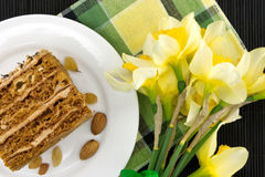 Cake slice with nut on plate. Bouquet of yellow daffodil Stock Image