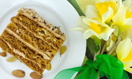 Cake slice with nut on plate. Bouquet of yellow daffodil Stock Photography