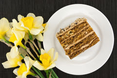 Cake slice with nut on plate. Bouquet of yellow daffodil Stock Photos