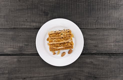 Cake slice with nut on plate on wooden table, top view. Cake slice with nut on plate, on wooden table, top view Stock Images