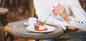 Cake slice on white plate. Cake with cream delicious dessert. Appetite concept. Dessert cake cup of coffee and female. Hand with fork close up. Piece of cake stock photography