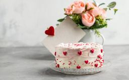 Cake with small hearts and colorful sprinkles on a plate with coffee. royalty free stock photo