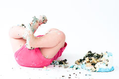 Cake Smash. Baby eating cake, covered in cake, lying on floor Royalty Free Stock Photos