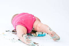 Cake Smash. Baby eating cake, covered in cake, lying on floor Royalty Free Stock Photography