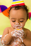 Cake smash closeup. Adorable african baby during a cake smash on his first birthday royalty free stock image