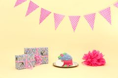 Cake-smash set. With cake (with blank name board), gift boxes and flags on cream background Royalty Free Stock Photography