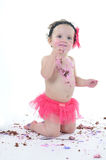 Cake smash shoot: Messy baby girl eating birthday cake! Royalty Free Stock Image