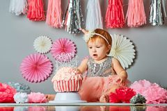 Cake Smash - Stock image. Portrait of cute adorable Caucasian baby girl with blue eyes in pink tutu skirt celebrating her first birthday with gourmet cake and royalty free stock photos