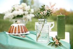 Cake with some cups on picnic table decorated with flowers, candles, vase in green field. Cake with some cups on picnic table decorated with flowers, candles Stock Photos