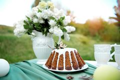 Cake with some cups on picnic table decorated with flowers, candles, vase in green field. Cake with some cups on picnic table decorated with flowers, candles stock photography