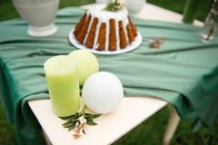 Cake with some cups on picnic table decorated with flowers, candles, vase in green field. Cake with some cups on picnic table decorated with flowers, candles Stock Images