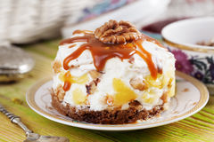 Cake with sour cream, whipped, boiled condensed milk, pineapple, walnuts, chocolate, biscuit, Royalty Free Stock Image