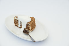 Cake and spoon. Honey cake with sour cream on white plate and spoon Stock Photo