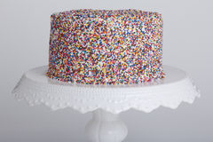 Cake with sprinkles. A cake with vanilla frosting that is encrusted in rainbow sprinkles. The cake was placed upon a vintage white cakestand and shot against a Stock Photo