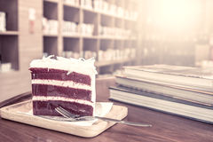 Cake and stack of books on wooden table Royalty Free Stock Images