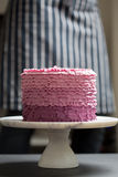 Cake on a stand. Handmade pink cake on a white stand Stock Photos
