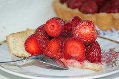 Cake with strawberries. Delicious strawberry cake on a white plate Stock Image