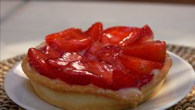 Cake with strawberries. Small strawberry cake is lying on a white plate stock footage