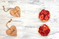 A cake with strawberries and a wooden heart on a white painted surface. Valentine`s Day. A cake with strawberries and a wooden heart on a white painted surface stock photos