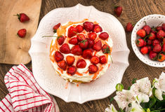 Cake. Strawberry cake with whipped cream in wooden table stock image