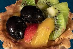 Cake Tartlet with fruit. Strawberry Grapes Kiwi Peach stock photo