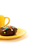 Cake and tea. Chocolate cake on the yellow plate and cup of tea royalty free stock images